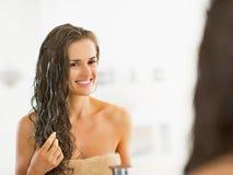 Lycklig ung kvinna som applicerar hårmaskeringen i badrum arkivbild