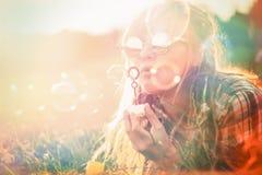 Lycklig ung kvinna som blåser såpbubblor arkivfoton