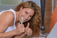 Lycklig ung kvinna som borstar hennes tänder Arkivbild