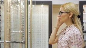 Lycklig ung kvinna som försöker nya exponeringsglas på optikerlagret lager videofilmer