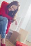 Lycklig ung kvinna som försöker på skodon i lager arkivfoto