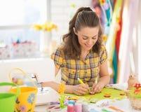 Lycklig ung kvinna som gör easter garnering royaltyfri fotografi