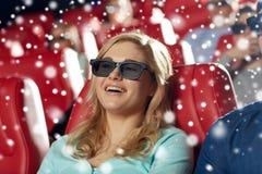 Lycklig ung kvinna som håller ögonen på filmen 3d i teater Arkivbild