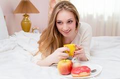 Lycklig ung kvinna som har frukosten i säng Arkivbilder