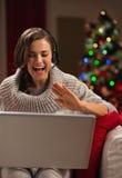 Lycklig ung kvinna som har video pratstund med familjen Arkivfoto