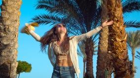 Lycklig ung kvinna som hoppar och har gyckel under palmträd i Egypten f?r sommarterritorium f?r katya krasnodar semester arkivfilmer