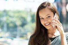 Lycklig ung kvinna som inomhus talar vid mobiltelefonen arkivfoton