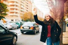 Lycklig ung kvinna som kallar för en taxi i staden Arkivbild