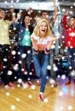Lycklig ung kvinna som kastar bollen i bowlingklubba Royaltyfria Foton