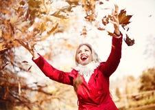 Lycklig ung kvinna som kastar höstsidor Arkivfoton