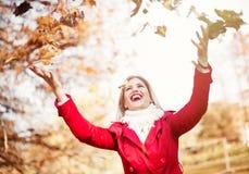 Lycklig ung kvinna som kastar höstsidor Fotografering för Bildbyråer