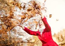 Lycklig ung kvinna som kastar höstsidor Arkivbild