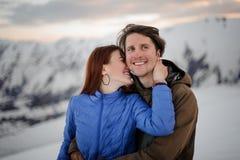 Lycklig ung kvinna som kysser hennes le pojkvän i berg royaltyfria foton