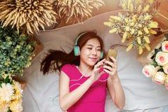Lycklig ung kvinna som lägger på golvet till lyssnande musik via Sma Arkivbild