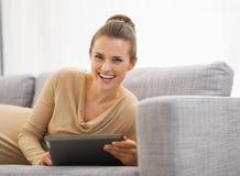 Lycklig ung kvinna som lägger på soffan med minnestavlaPC Royaltyfri Bild