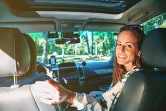 Lycklig ung kvinna som ler sammanträde inom av bilen arkivbild