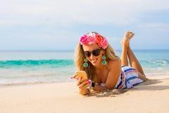 Lycklig ung kvinna som ligger på stranden i sand och använder mobiltelefonen arkivbilder