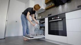 Lycklig ung kvinna som ordnar plattor i diskaren At Home arkivfilmer