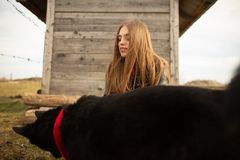 Lycklig ung kvinna som plaing med hennes svarta hund i fron av det gamla tr?huset Flickan f?rs?ker en hatt till hennes hund arkivbild
