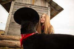 Lycklig ung kvinna som plaing med hennes svarta hund i fron av det gamla tr?huset Flickan f?rs?ker en hatt till hennes hund royaltyfri fotografi