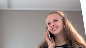 Lycklig ung kvinna som pratar på hennes mobil arkivfilmer