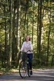 Lycklig ung kvinna som rider en cykel royaltyfria bilder