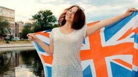 Lycklig ung kvinna som rymmer den Storbritannien flaggan lager videofilmer