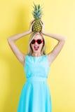Lycklig ung kvinna som rymmer en ananas Royaltyfri Fotografi