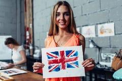Lycklig ung kvinna som rymmer en bild av den brittiska flaggan dragen med vattenfärgteknik under konstterapi för vuxna människor Arkivbilder