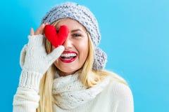 Lycklig ung kvinna som rymmer en hjärtakudde Arkivbild