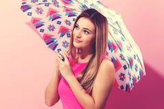 Lycklig ung kvinna som rymmer ett paraply Royaltyfria Bilder