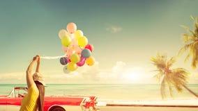 Lycklig ung kvinna som rymmer färgrika ballonger med att sväva arkivbild
