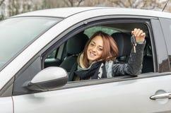 Lycklig ung kvinna som sitter i bilen som ler på kameran som visar tangenten royaltyfri fotografi