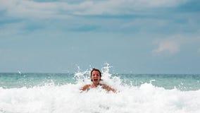Lycklig ung kvinna som spelar med att krascha vågor royaltyfri fotografi