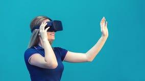 Lycklig ung kvinna som spelar på VR-exponeringsglas inomhus Virtuell verklighetbegrepp med unga flickan som har gyckel med hörlur royaltyfri fotografi