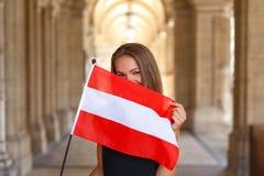 Lycklig ung kvinna som täcker hennes framsida med den österrikiska flaggan Arkivbild