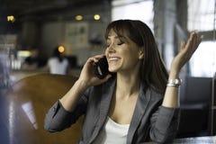 Lycklig ung kvinna som talar på telefonen i en coffee shop Royaltyfri Foto