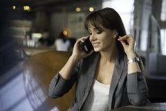 Lycklig ung kvinna som talar på telefonen i en coffee shop Arkivfoto