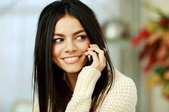 Lycklig ung kvinna som talar på telefonen och åt sidan ser Arkivfoto