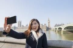 Lycklig ung kvinna som tar självståenden till och med mobiltelefonen mot Big Ben på London, England, UK Royaltyfri Fotografi