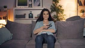 Lycklig ung kvinna som vänder på den hållande ögonen på showen för TV som hemma ler på natten lager videofilmer