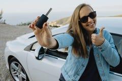Lycklig ung kvinna som visar nya tangenter för uthyrnings- bil Arkivbilder