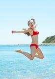 Lycklig ung kvinnabanhoppning på sjösidan royaltyfria foton