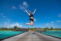 Lycklig ung kvinnabanhoppning på stranden arkivfoton
