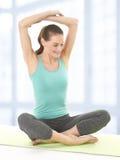 Lycklig ung kvinnasträckning beväpnar på matt Yoga Arkivbild