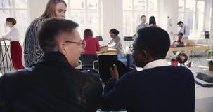 Lycklig ung kvinnlig chef som talar till multietniska manliga kollegor som tillsammans arbetar på det bekväma moderna vindkontore arkivfilmer