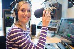 Lycklig ung kvinnlig radiovärdsradioutsändning i studio Royaltyfri Foto