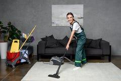lycklig ung kvinnlig rengörande företagsarbetare som använder dammsugare och att le arkivfoton