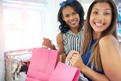 Lycklig ung kvinnlig shoppare som grinar på kameran royaltyfria bilder
