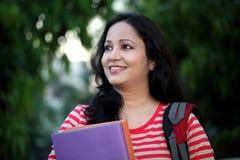 Lycklig ung kvinnlig student på högskolauniversitetsområdet royaltyfria bilder